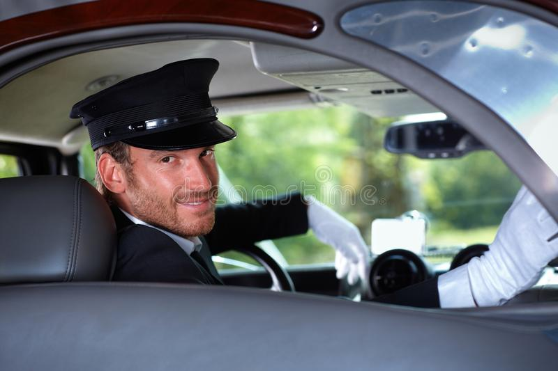 Smiling chauffeur in limousine. Handsome young chauffeur in limousine, smiling royalty free stock photos