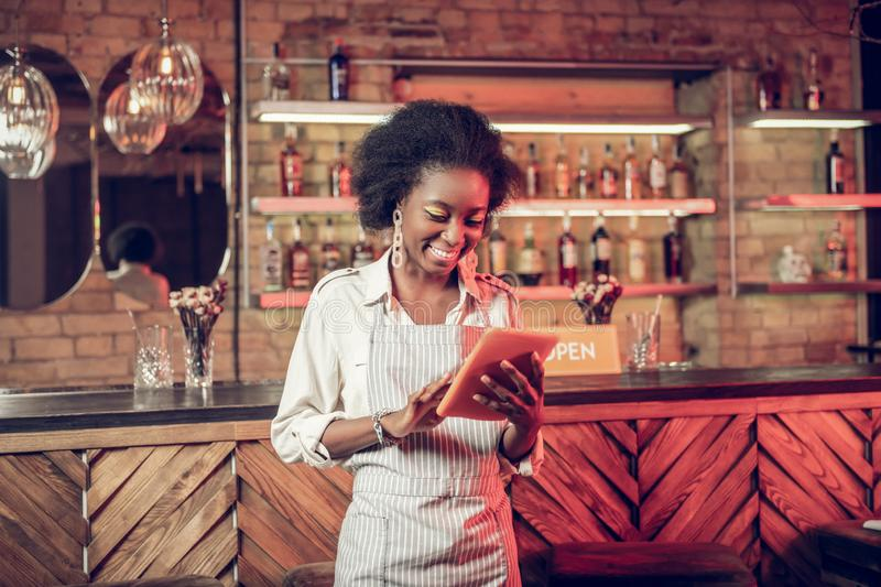 Smiling cheerful Afro-American bar waitress adding order information to tablet royalty free stock image