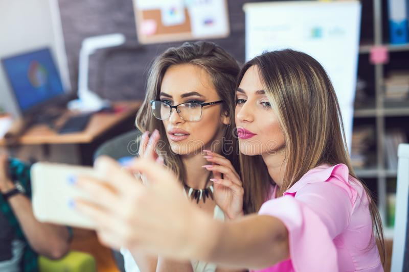 Smiling cheerful business women taking a selfie in the office stock image