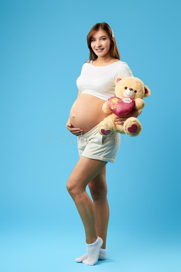 Cheerful girl with long brown hair has prepared a tiy for her future baby. Smiling cheerful girl with long brown hair has prepared a tiy for her future baby stock image