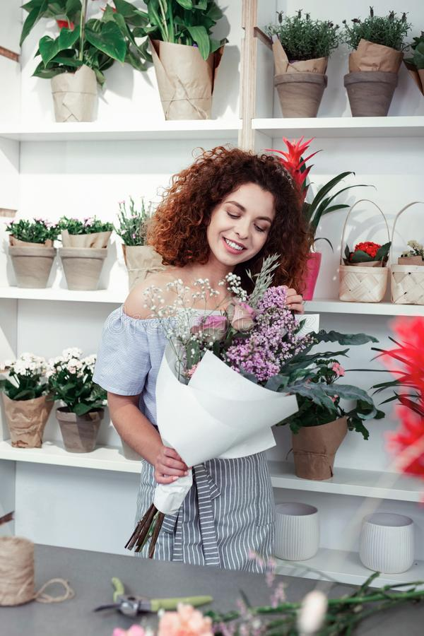 Smiling cheerful lady correcting elements of stylish bouquet royalty free stock image