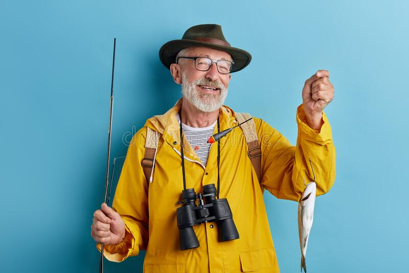 Smiling cheerful old fishman boasting about his catch. Close up photo. isolated blue background royalty free stock image