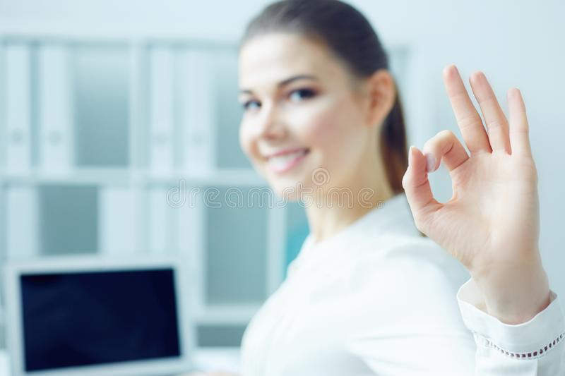 Smiling student girl happy with completed work showing OK gesture, sitting half turn looking in camera while working on royalty free stock images