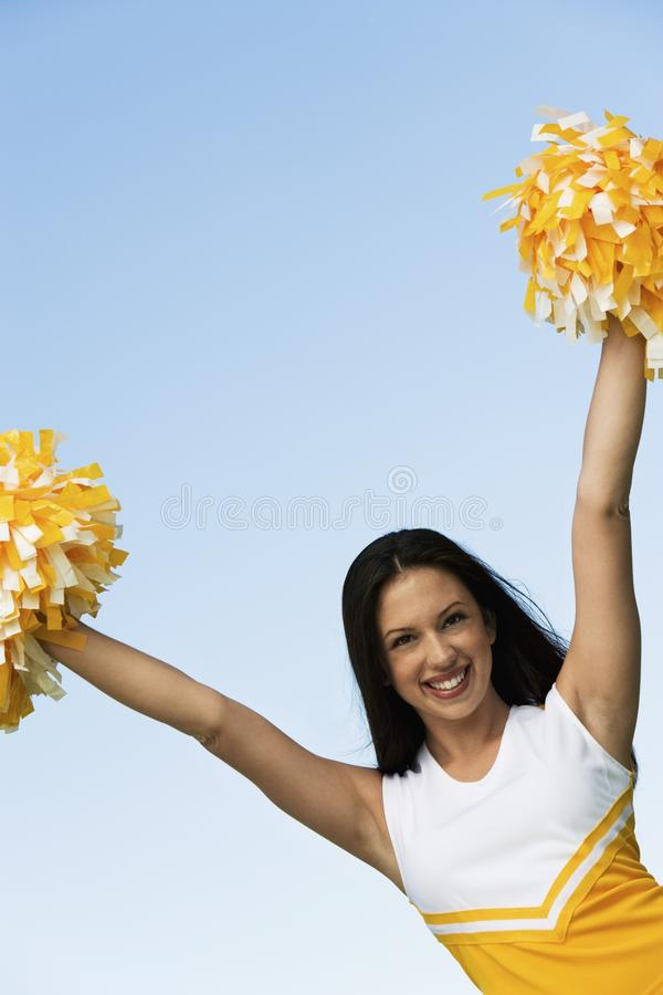 Smiling Cheerleader Rising Pom-poms Stock Photography