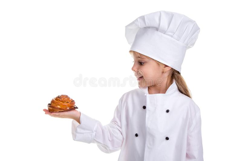 Smiling chef girl in a cap cook uniform, holding the bun in the right hand. Looking at the bun royalty free stock photo