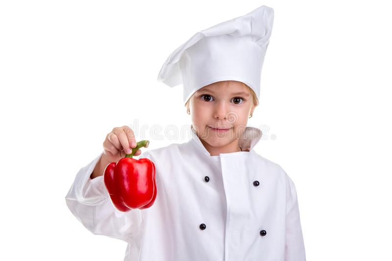 Smiling chef girl in a cap cook uniform, holding with one hand the red bell pepper tail. Human emotions, facial stock image