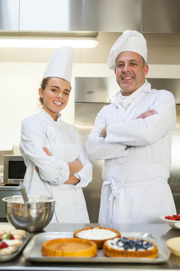 Smiling chef and head chef standing arms crossed. Looking at camera stock photos