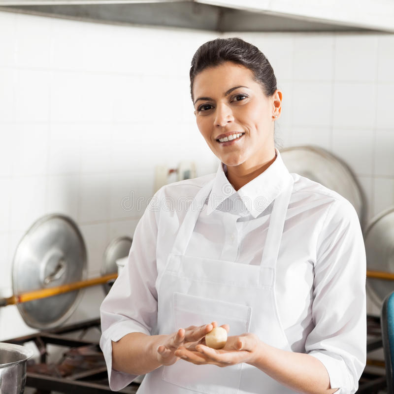 Smiling Chef Holding Pasta Dough Ball In Kitchen. Portrait of smiling female chef holding pasta dough ball in commercial kitchen stock photo