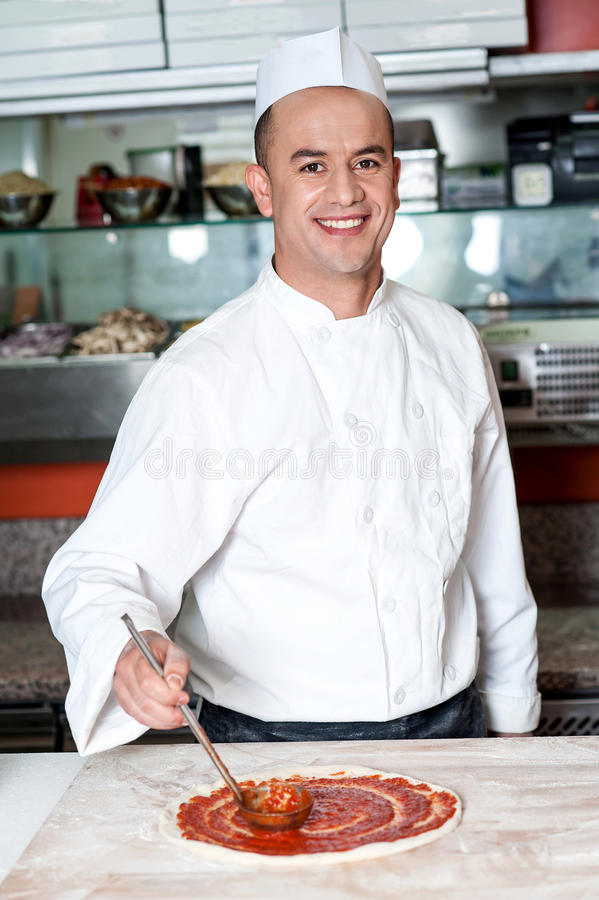 Smiling chef making pizza royalty free stock photography