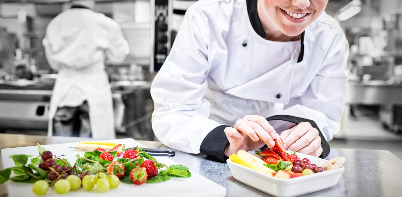 Smiling chef putting a strawberry in the fruit bowl royalty free stock photography