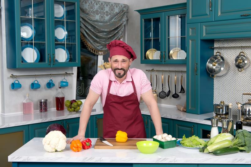 Smiling Chef in red apron and red bonnet standing at kitchen tab. Le with vegetables. Fresh vegetables prepared to be cut by guy at kitchen. Man loves cooking royalty free stock images