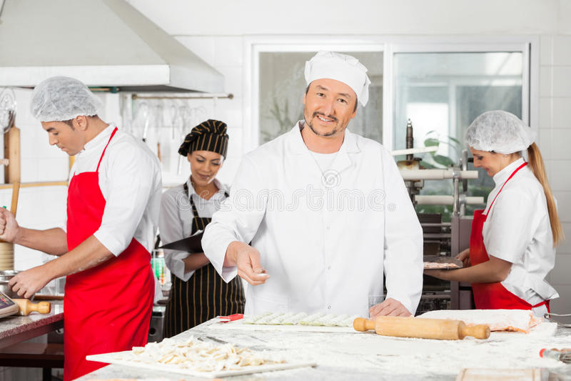 Smiling Chef Sprinkling Flour On Ravioli Pasta In. Portrait of smiling male chef sprinkling flour on ravioli pasta with colleagues working in background at stock images