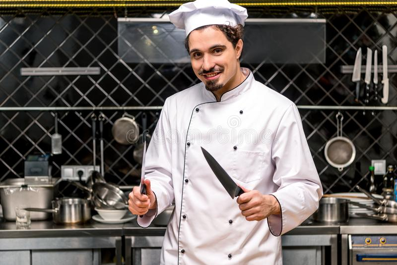 Smiling chef standing with knifes. In kitchen royalty free stock images