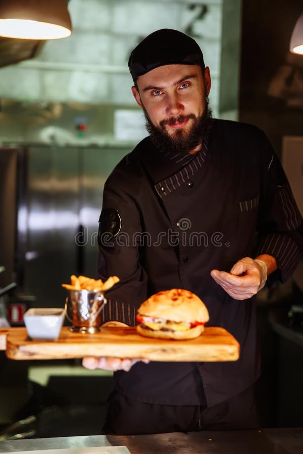 Smiling master chef in uniform looking at camera, holding plate with served burger. stock photos