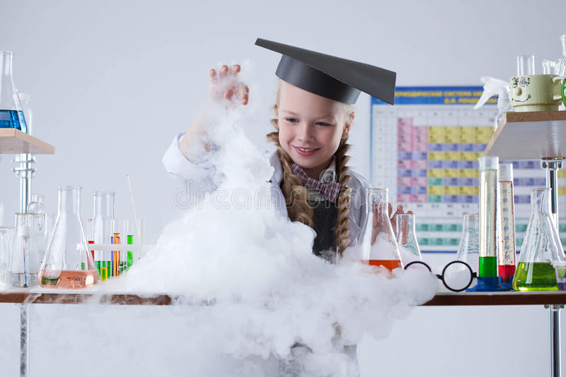 Smiling chemist observes reagent's vaporization stock photos