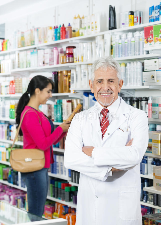 Smiling Chemist Standing Arms Crossed While Woman Choosing Produ stock photo