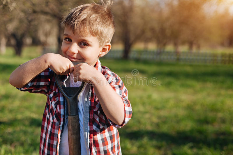 Smiling chestnut haired boy with spade in garden. Charming helpmeet. Adorable hazel-eyed child wearing a plaid shirt leaning on a shovel and looking into the stock images