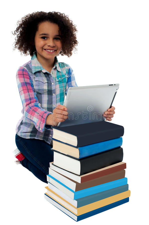 Download Smiling Child Busy With Tablet Pc And Books Stock Photo - Image: 31602904