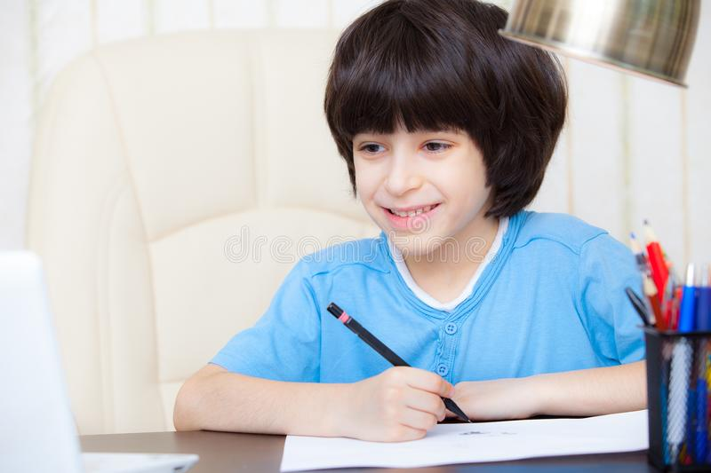 Smiling child doing homework with computer stock image
