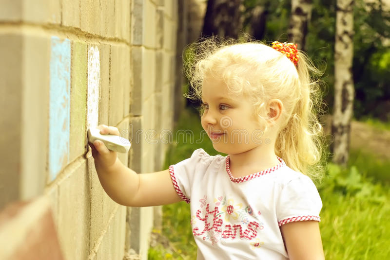 Smiling child drawing with chalk on the wall. Outdoors, candid stock image