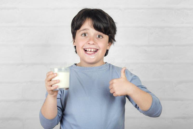 Smiling child drinking milk. Against brick background stock photo