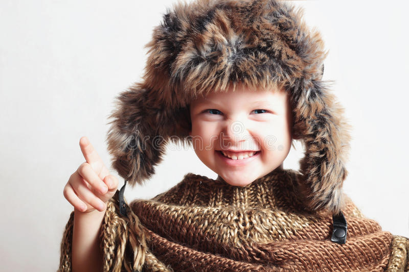Smiling child in fur Hat.Kids casual winter style.fashion little funny boy.children emotion. Portrait of smiling child in fur Hat.Kids casual winter style stock images