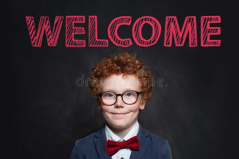 Smiling child with ginger hair portrait. Cute little boy in blue suit against blackboard with welcome inscription royalty free stock photos