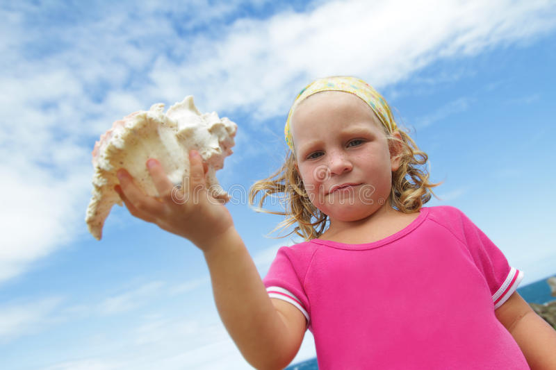 Smiling Child Girl With Big Sea Shell Stock Image