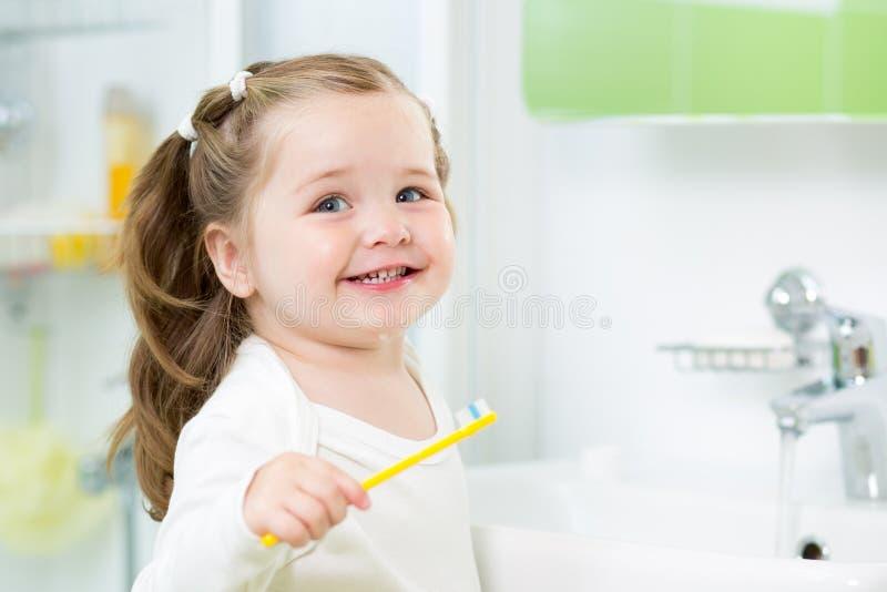 Smiling child girl brushing teeth royalty free stock images