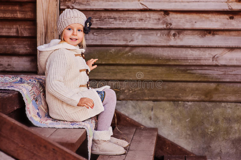 Smiling child girl at country house sitting on stairs. Cute smiling child girl at country house sitting on stairs royalty free stock photos