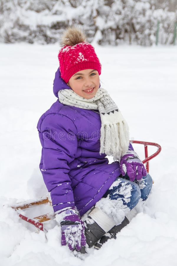 Child girl in snowy park on sledge royalty free stock image