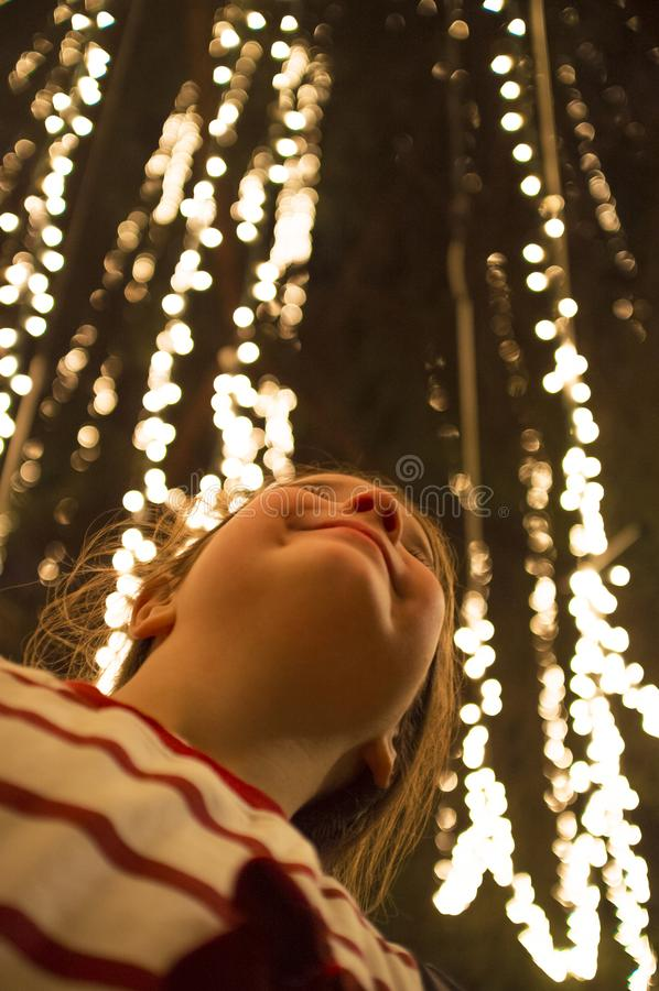 Smiling child girl under urban tree wrapped up with Xmas string led lights. Smiling child girl under urban tree wrapped up with Christmas string led lights. Low royalty free stock photo
