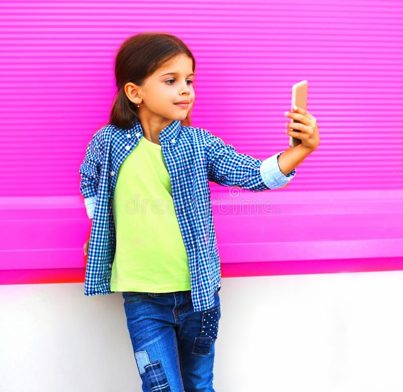 Smiling child taking selfie by smartphone in city on colorful wall stock images