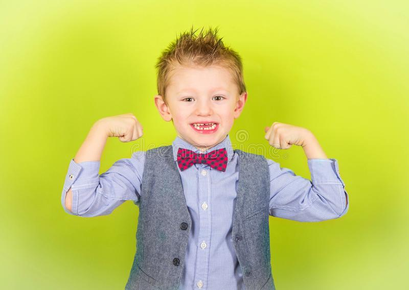 Smiling child who shows muscles royalty free stock photography