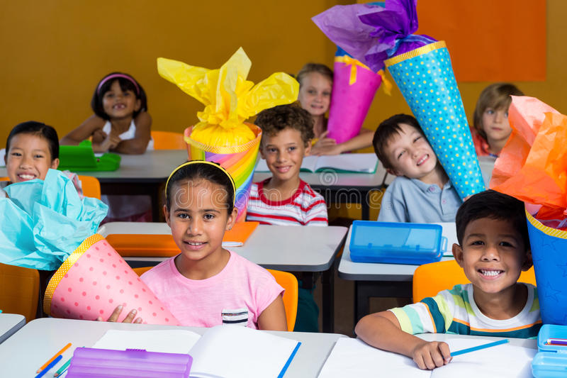 smiling children with craft work sitting on bench stock image