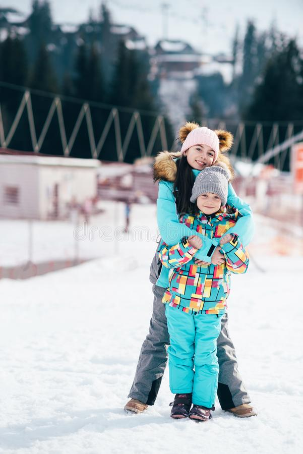 Smiling children enjoying winter vacations in mountains . Ski, Sun, Snow and fun royalty free stock images