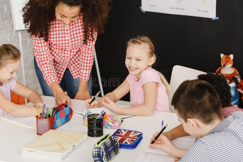 Smiling children and female teacher stock photos