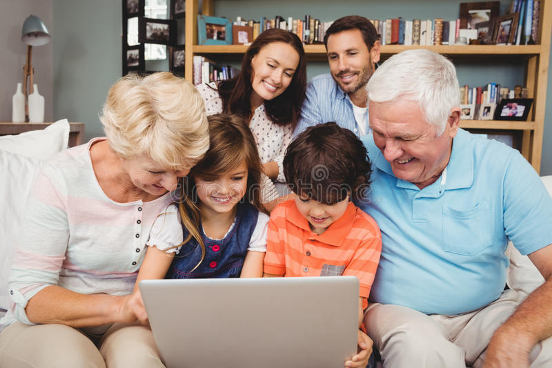 Smiling children and grandparents using laptop with family stock image