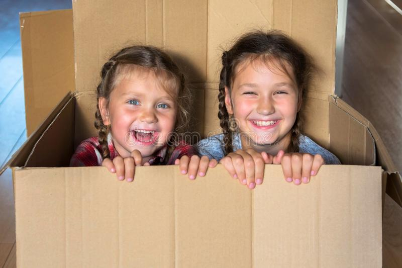 Smiling children look out of cardboard box. Moving concept royalty free stock image