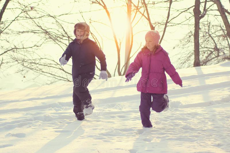 Smiling children playing on snow in winter holiday royalty free stock photo