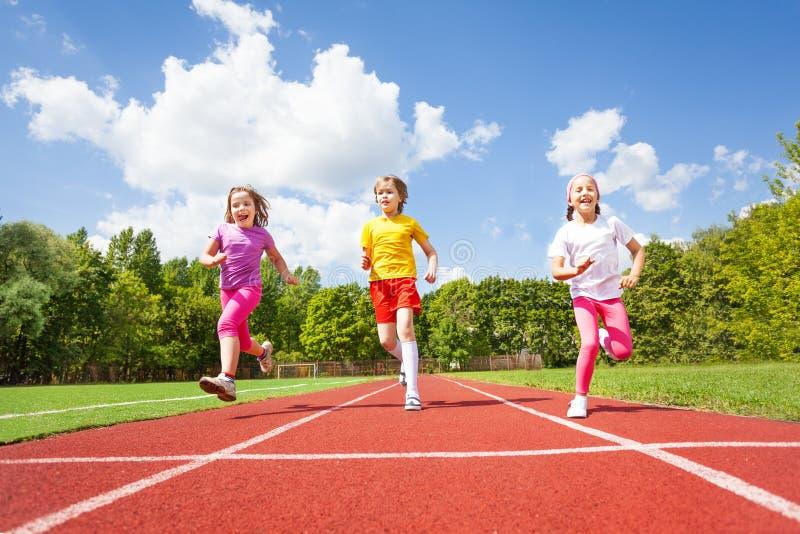 Smiling children running marathon together stock photos