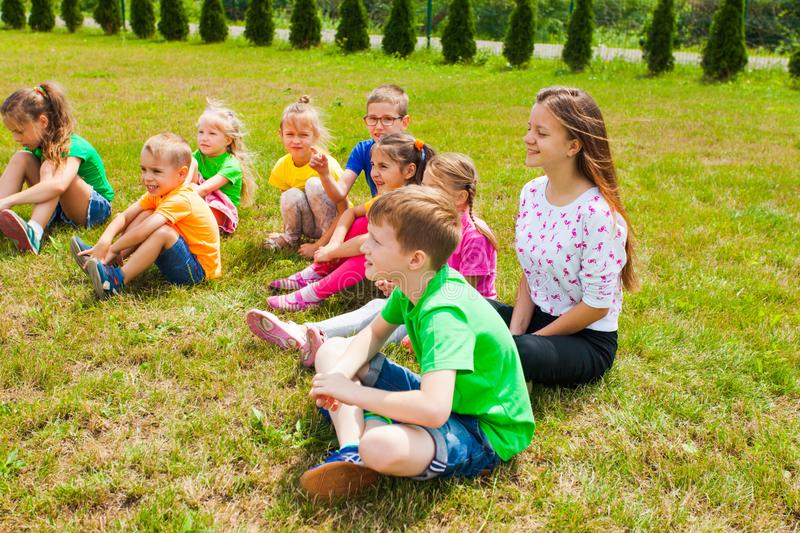 Smiling children sitting on a grass at outdoor lesson royalty free stock photos
