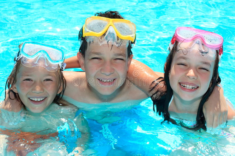 Smiling children in swimming pool. Three happy, smiling children in a swimming pool royalty free stock image