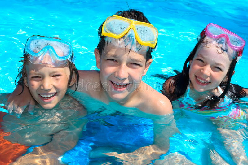 Smiling children in swimming pool. Three happy, smiling children with swimming goggles in a pool stock image