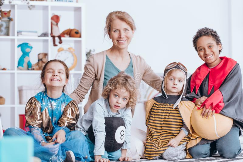 Smiling children and teacher. Portrait of smiling children in costumes and teacher in classroom of preschool royalty free stock images