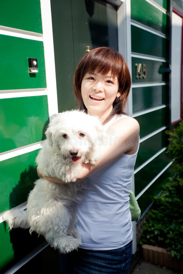 Smiling chinese girl with dog stock photo