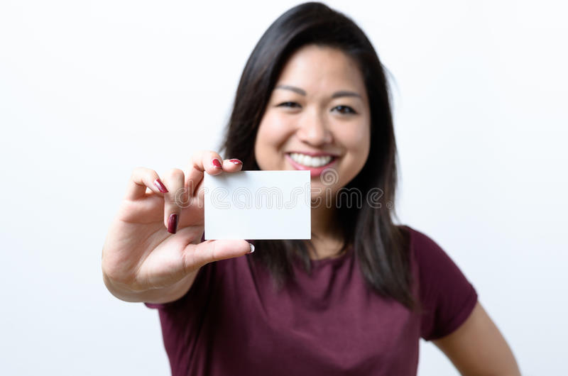 Smiling Chinese woman holding a business card stock photography