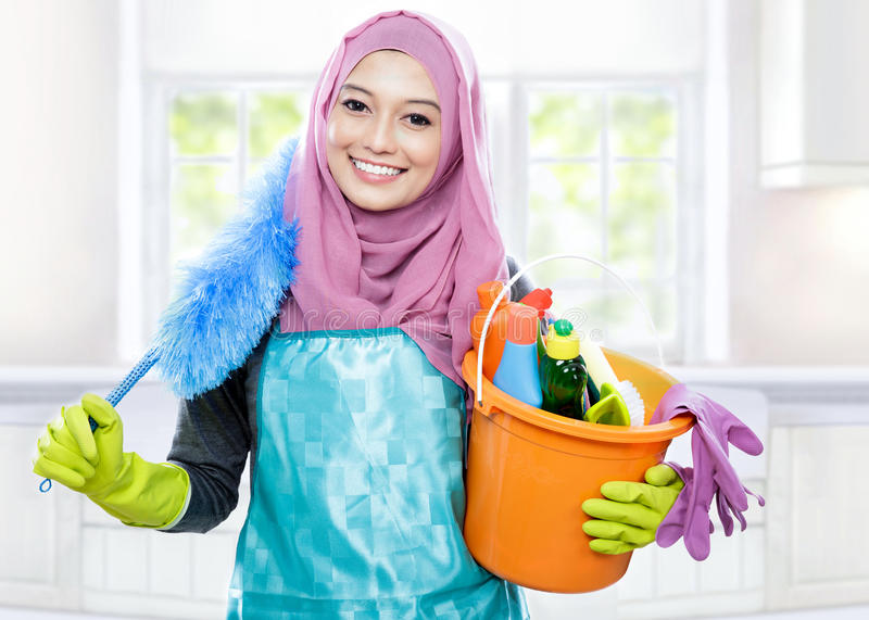Smiling cleaner young woman wearing hijab royalty free stock images