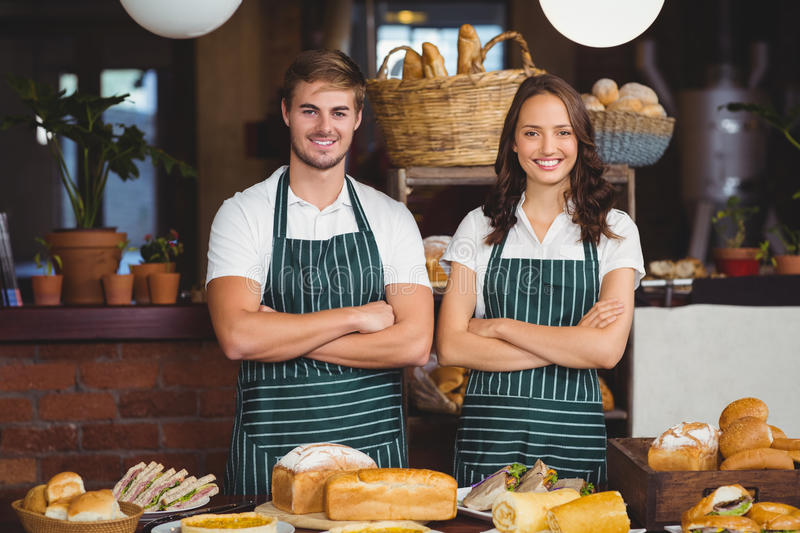 Smiling co-workers with arms crossed. Portrait of co-workers with arms crossed at the coffee shop royalty free stock photo