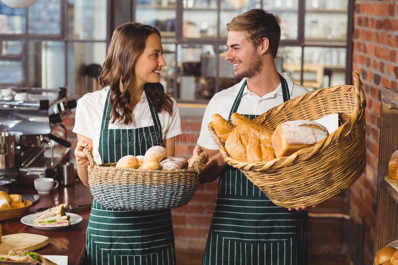 Smiling co-workers holding breads basket. At the coffee shop stock photos